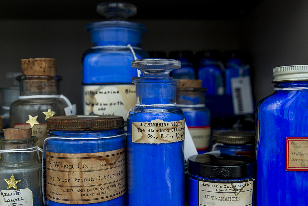 A group of blue pigments in jars of various shapes and sizes placed next to one another in the cabinet.