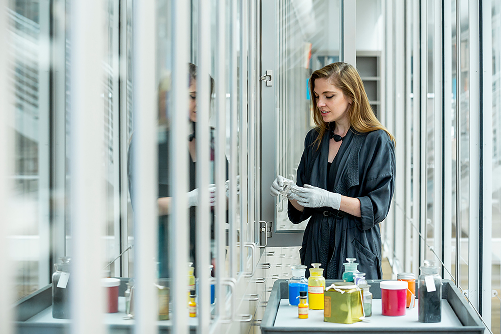 Woman standing beside the Forbes Pigment Collection cabinets handles materials with gloved hands and has a tray of pigments and materials in front of her.