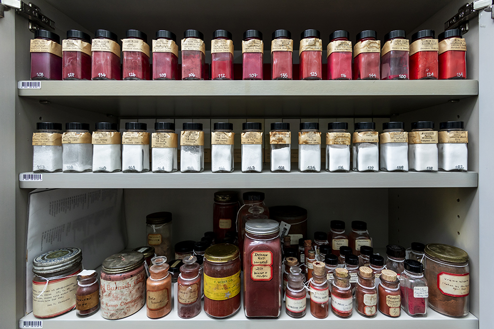 Three shelves lined with pigments, the top being red, the middle white, and the bottom red.