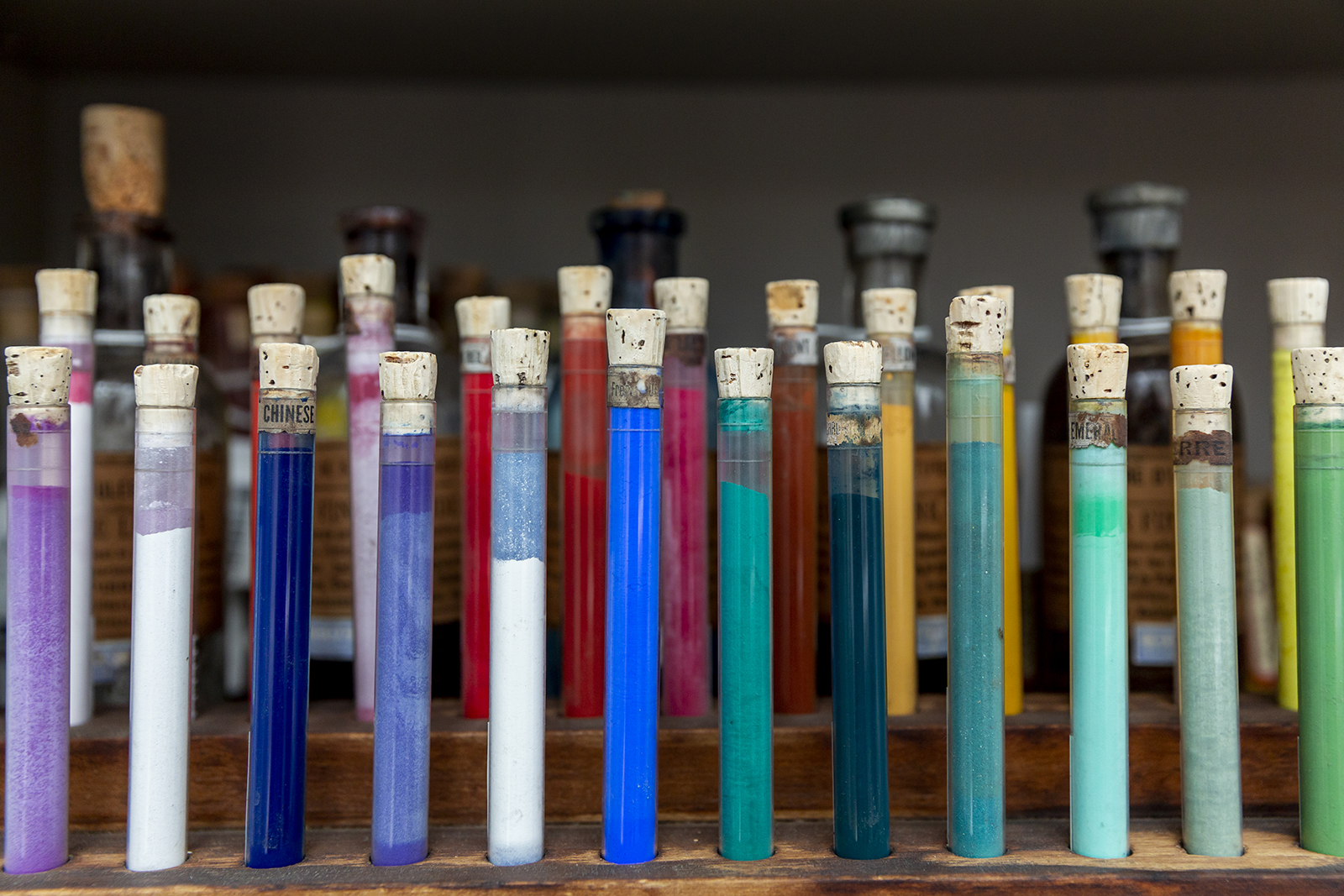Group of glass sample tubes in a wooden container, displaying pigments of a variety of colors including purples, blues, and greens.