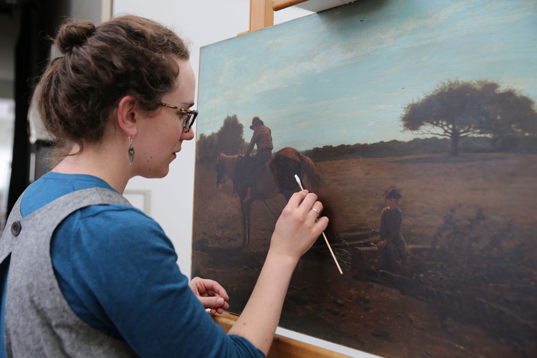 Schaffer uses a swab and solution to remove the varnish from the painting on the backside of the horse.