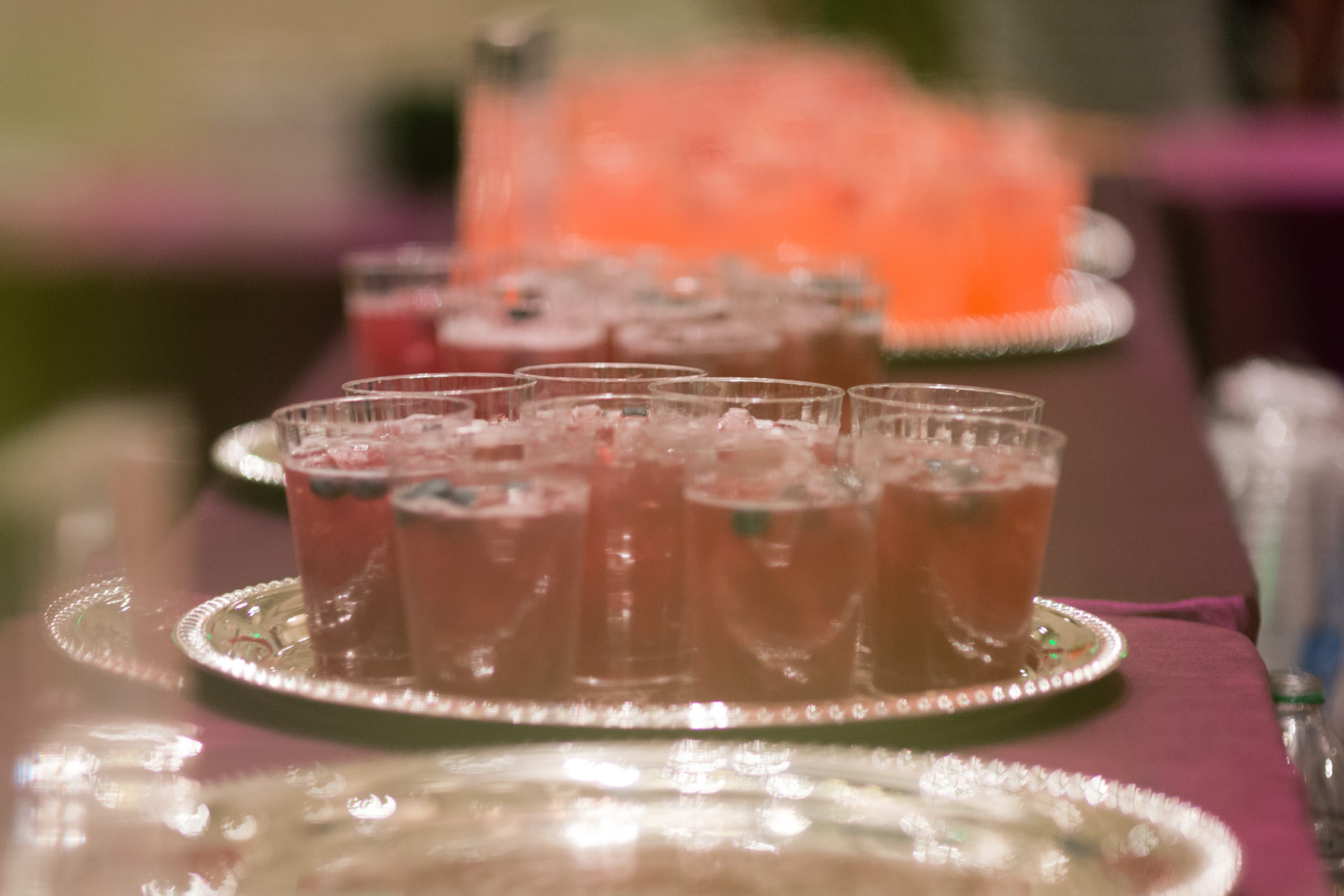 A group of non-alcoholic, colorful drinks on a silver tray
