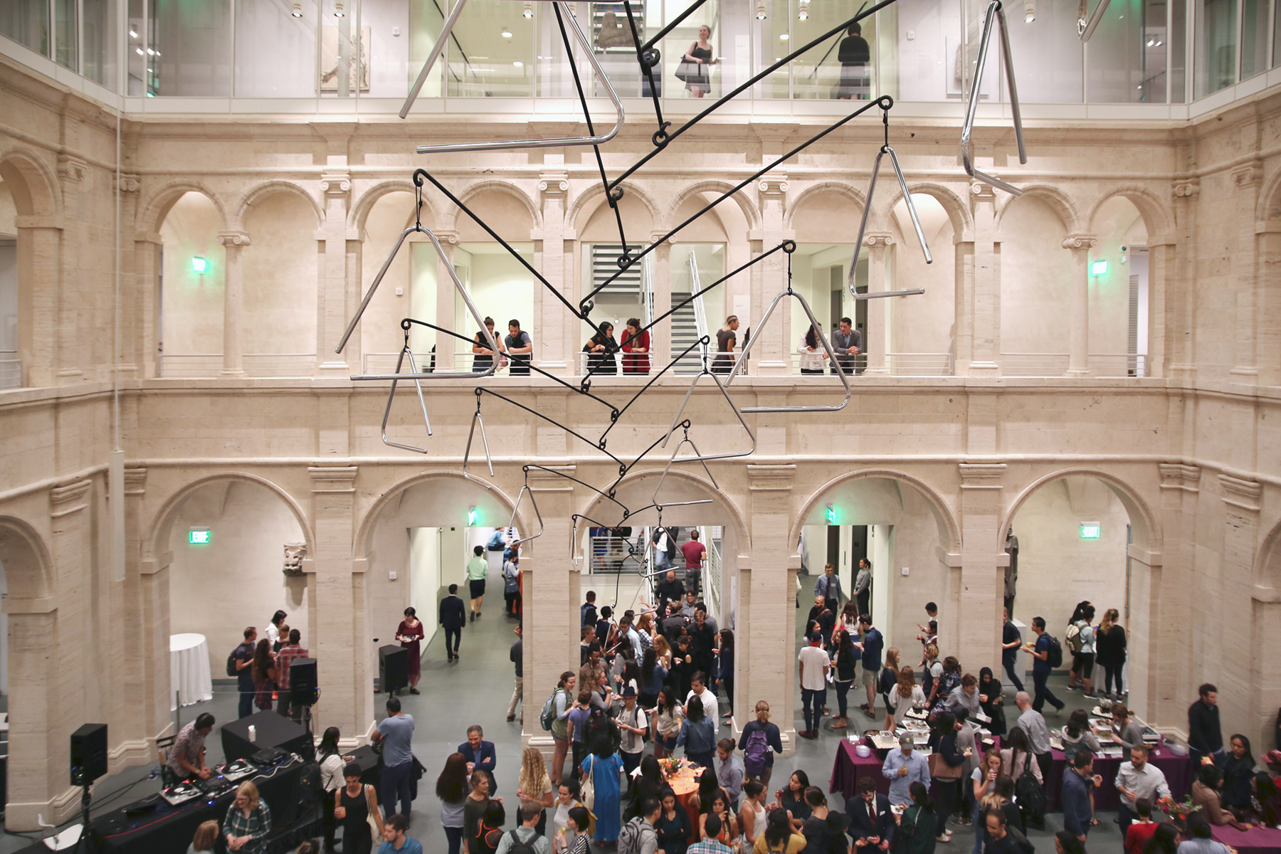 A picture of students mingling beneath a large hanging sculpture composed of instrumental triangles