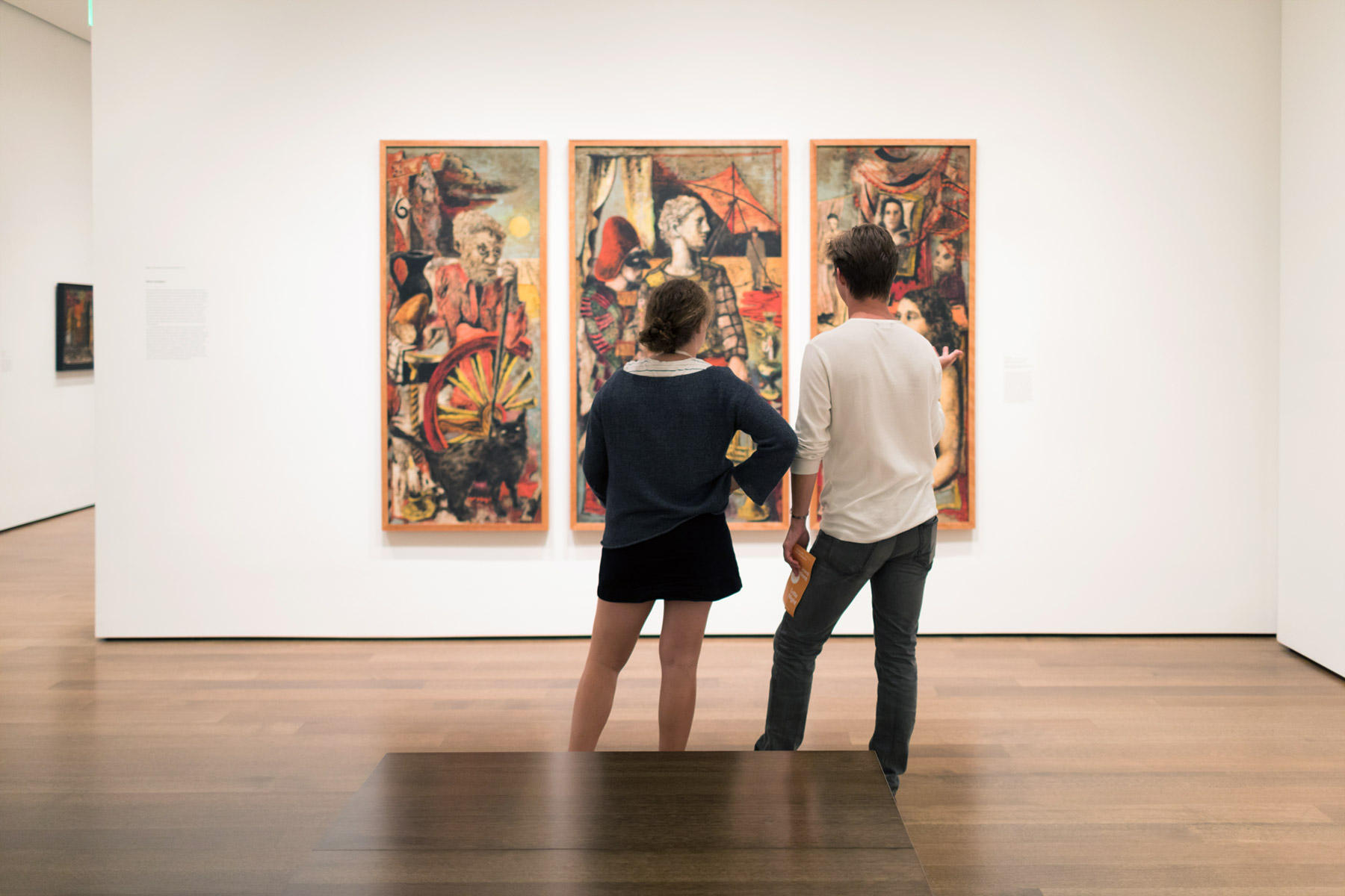 "Two students stand with their backs to the camera, facing a Erich Heckel's triptych ""To the Convalescent Woman."""