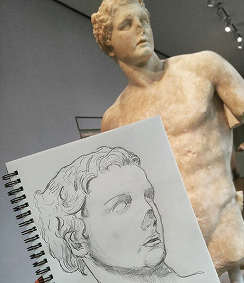 A sketchbook with a drawing of a sculpture of a man with a deteriorated nose, held up in front of the original object