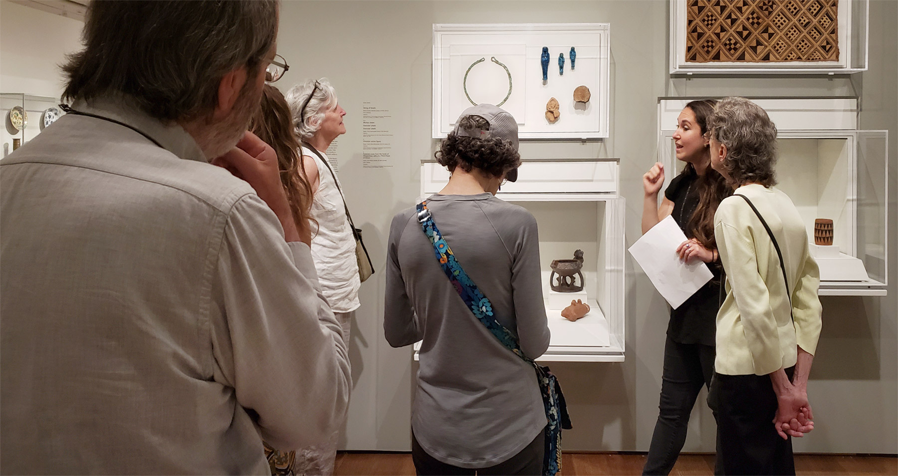 A group of people look toward a display case of art as Jen Thum, holding notes in her hand, talks to the visitors