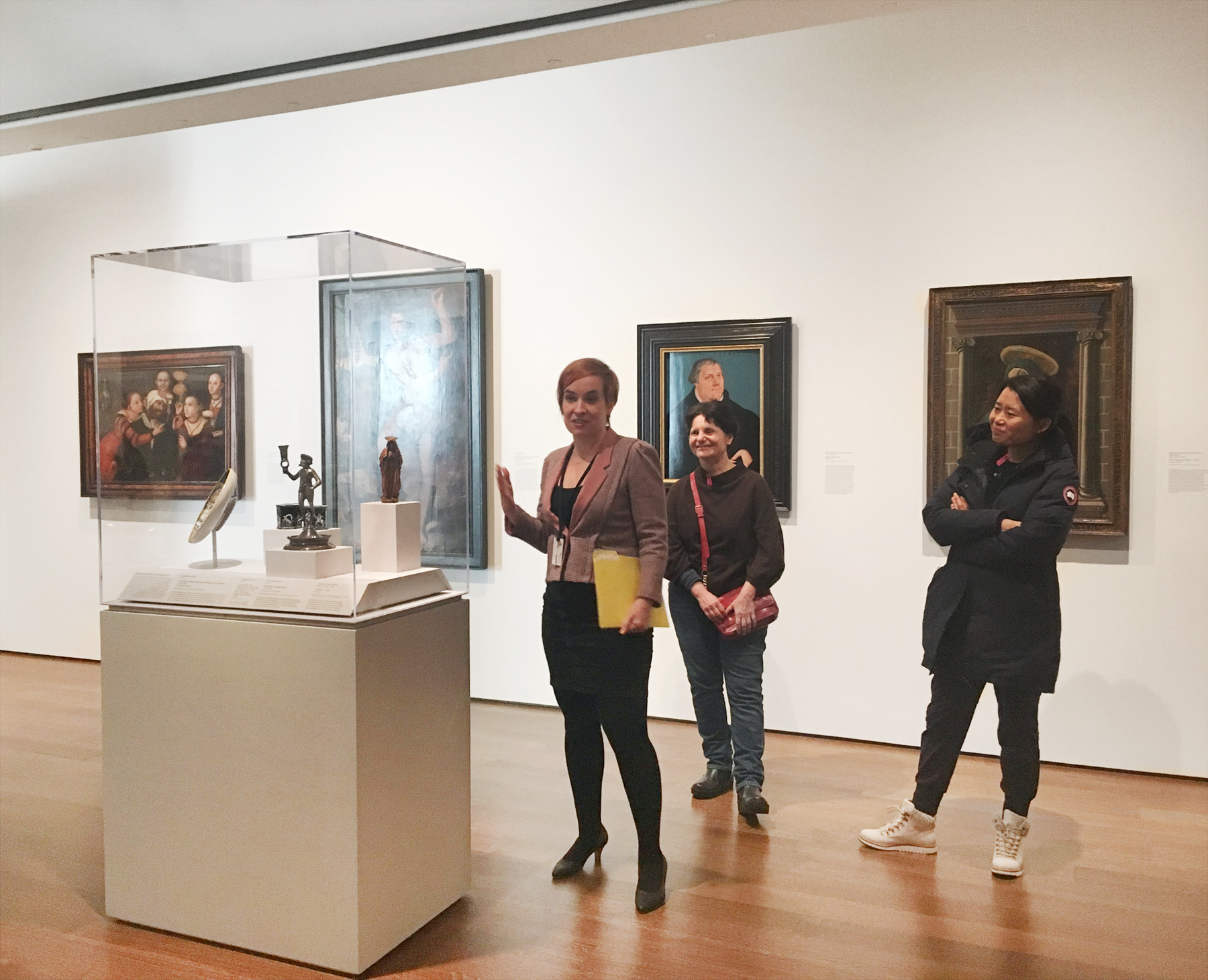Szalay stands next to a display case in the center of the Renaissance gallery, discussing the contents inside. Four paintings hang on the wall behind her and guests stand beside her.