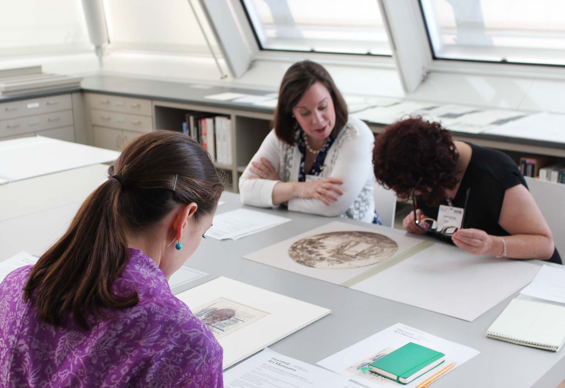 Three people sit at a table to view various prints in the Art Study Center