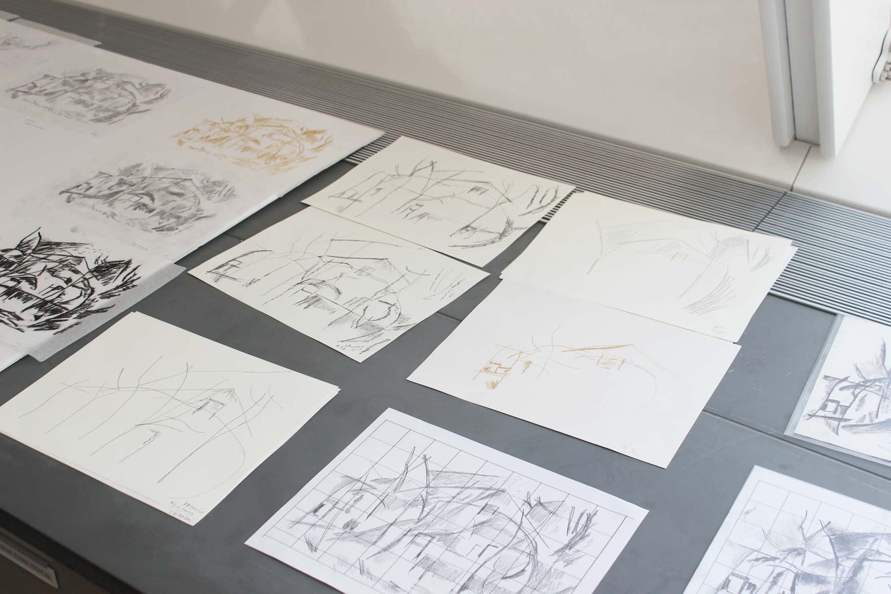 A group of drawings on a table imitating Sheeler's landscape drawing.