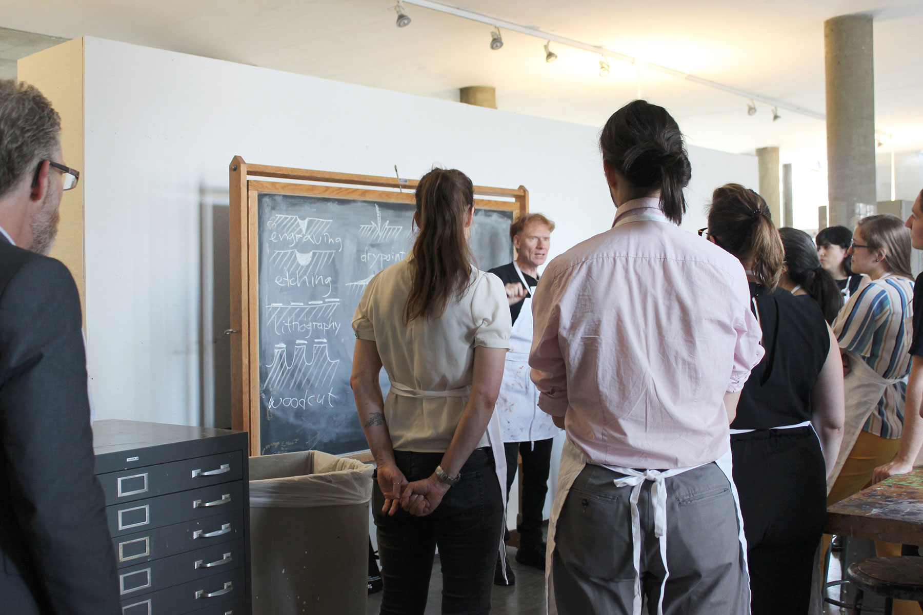 Stijnman, wearing a white apron, stands in front of a chalkboard explaining various printmaking techniques to several workshop participants.