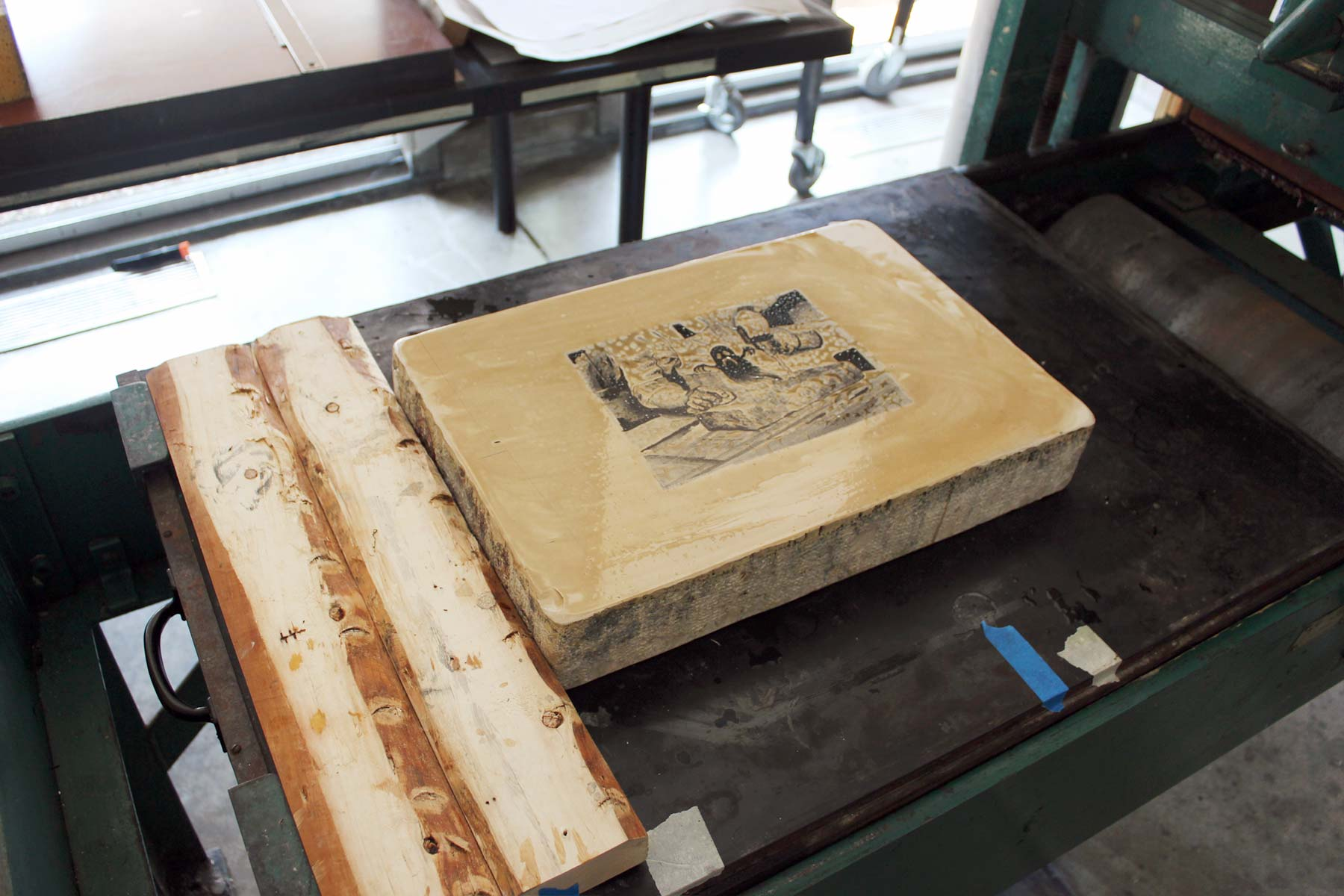 A lithography block depicts an image of a lithographer making a lithograph.