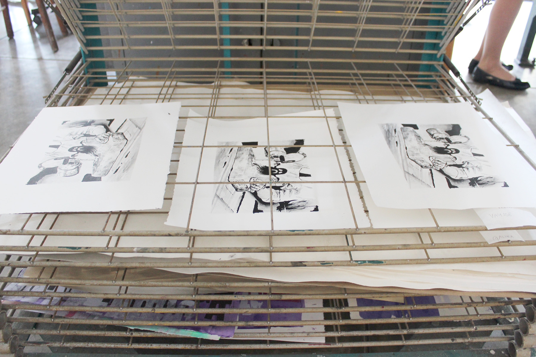 Three black and white prints sit atop a drying rack.