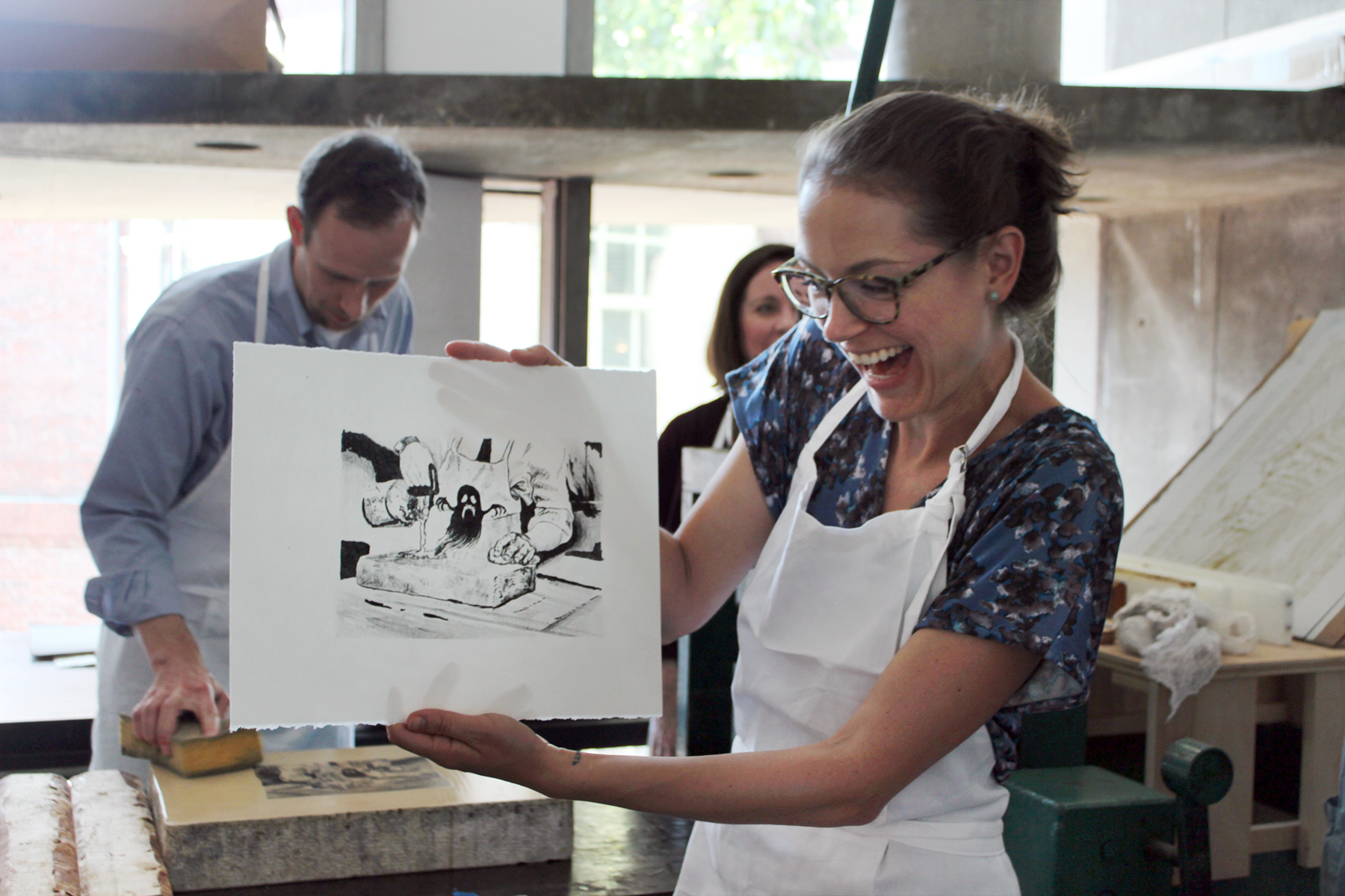 Mardilovich smiles and looks at the lithograph she made in the workshop.