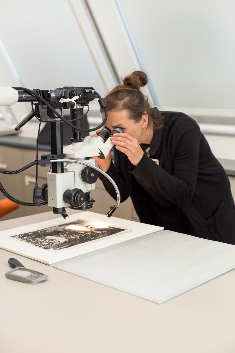 Zaunbauer looks into a microscope at the etching by Kirchner.
