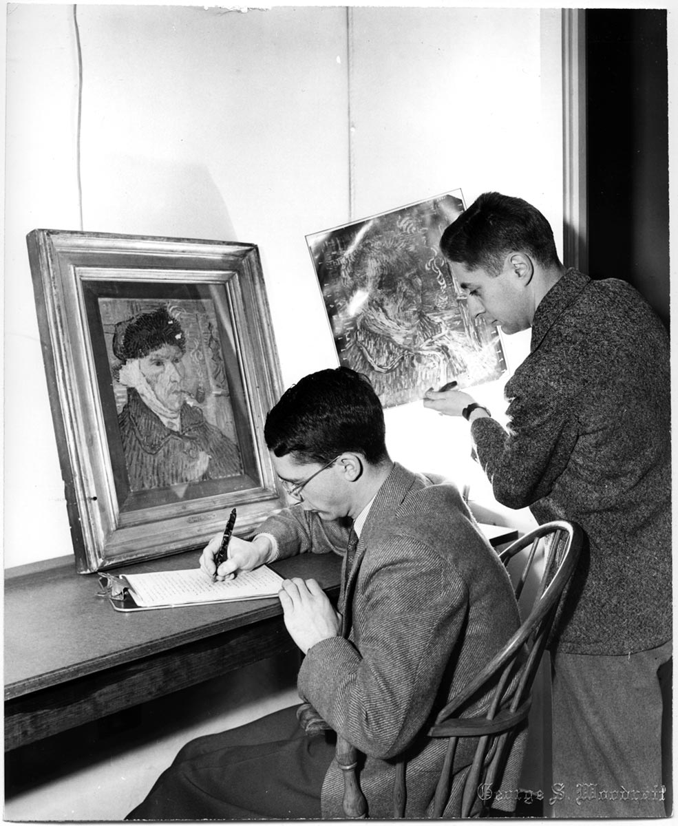 One student sits in front of a forged copy of Van Gogh's painting while another student standing close by, holding an X-ray of the original work.