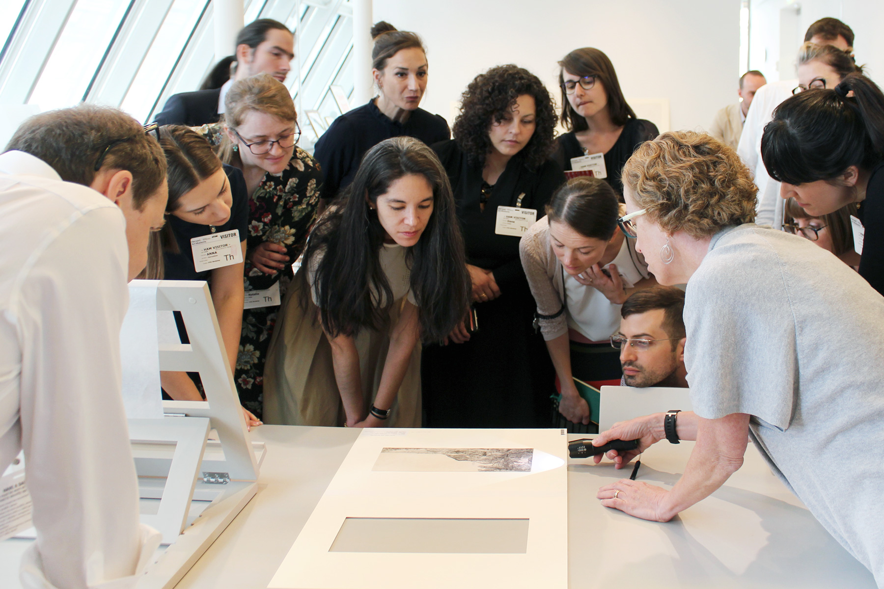Several participants look on as Knipe holds a light to a print, just under the matted frame, and Kunz stands nearby.