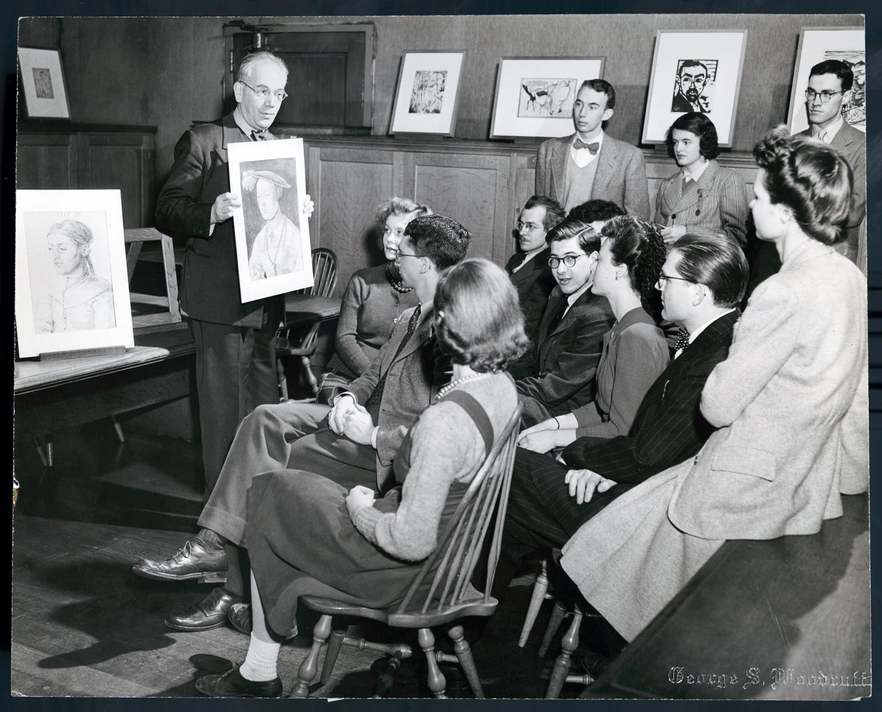 Rosenberg stands in front of a classroom holding a print to show students, some of whom are sitting and some of whom are standing. Another print sits on a nearby easel, and several prints rest on a shelf along the wall.