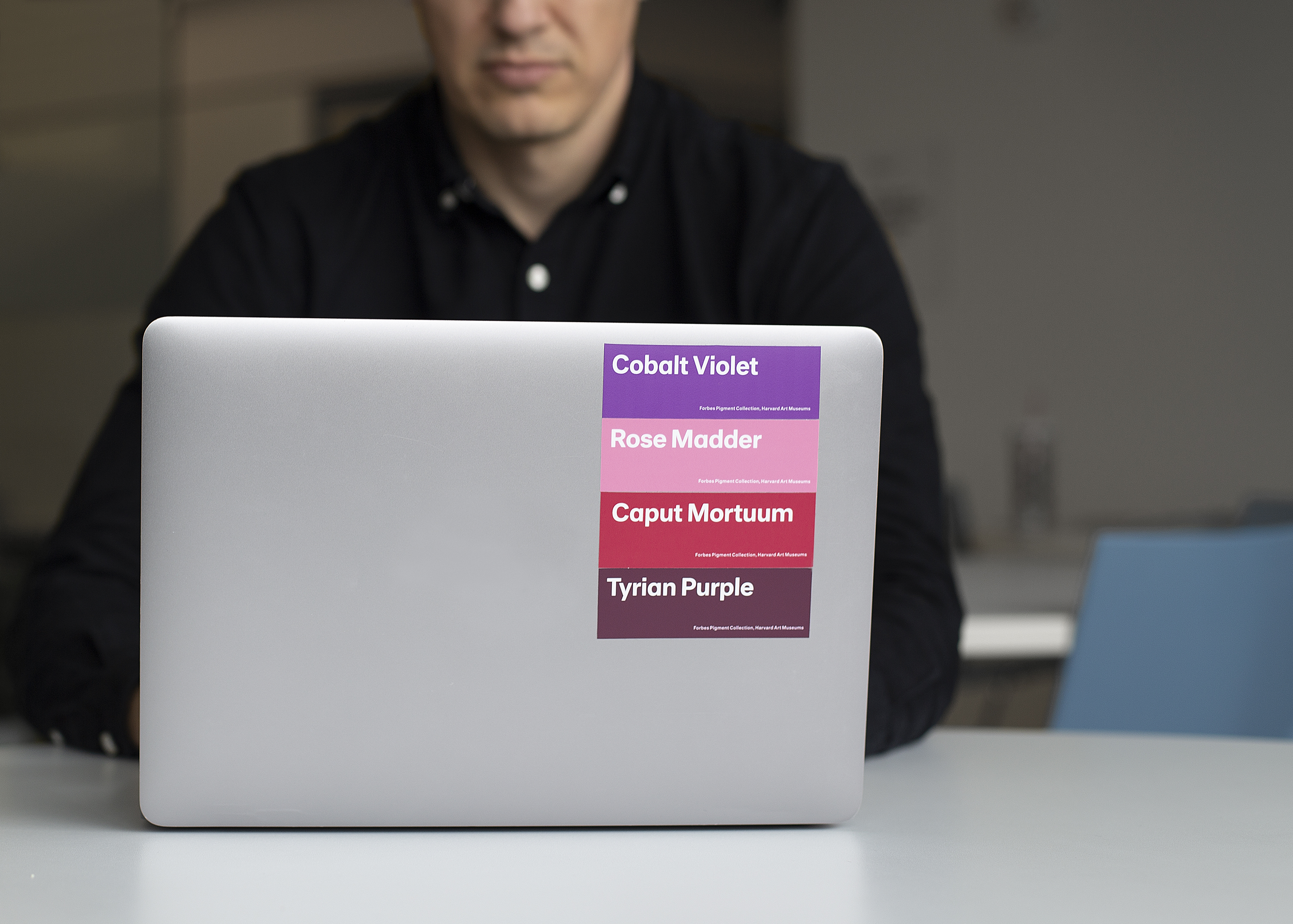 A man sits at a laptop, his face cropped in the photo. There are four stickers on his laptop, labeled from top to bottom: Cobalt Violet (light purple), Rose Madder (pink), Caput Mortuum (dark red), and Tyrian Purple (purple).