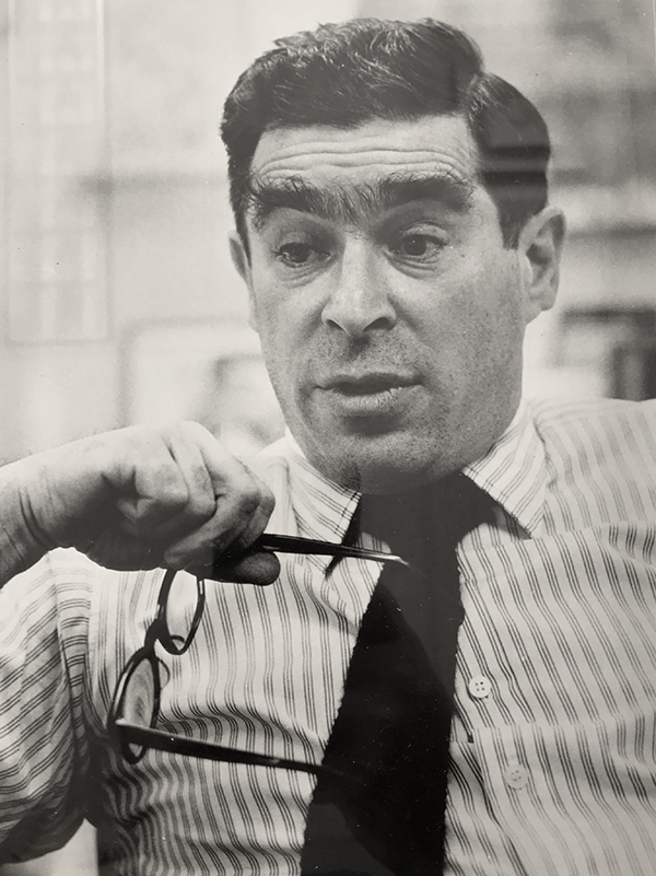 A black and white photograph depicts Werner Kramarsky, wearing a striped shirt and a tie, holding a pair of glasses.