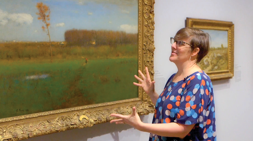 Smith stands in the gallery in front of a gold-framed landscape; she gestures with her hands while looking at the work. She has brown hair, wears glasses, and her purple blouse has blue, orange-red, and light gray polka dots. The painting shows a green fi
