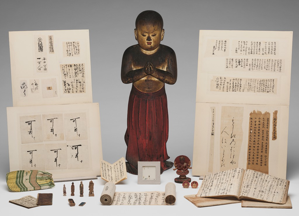 An image of a wooden figure stands on a grayish-white surface among various scrolls and objects. The figure's eyes are closed, and he holds his palms together in front of his body; a dark red pleated garment flows from his waist to his feet.