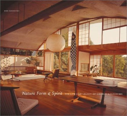 "This book cover shows a large room. The floor and furniture are a honey-colored wood. A large white paper lantern and a long fish decoration hang from the ceiling. The words ""Nature Form & Spirit THE LIFE AND LEGACY OF GEORGE NAKASHIMA."""