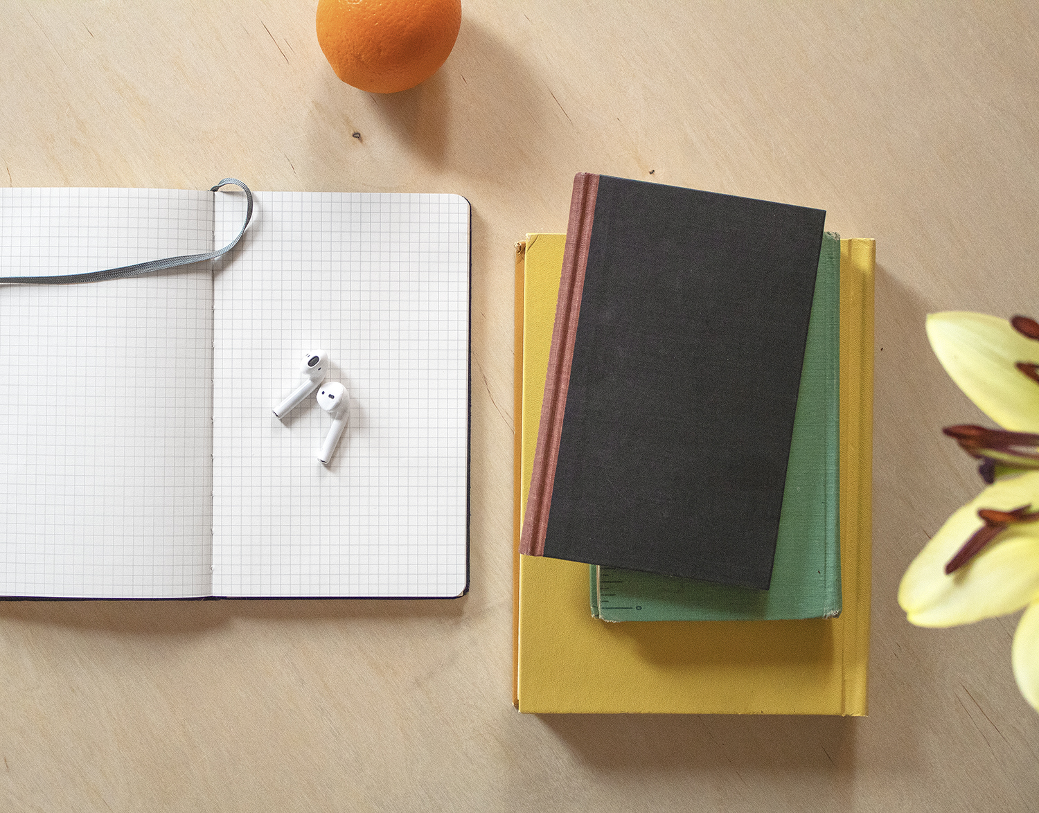 From the perspective of above, a grid-lined notebook lies open on a table, with earbuds on top. An orange is a few inches above the notebook and to the right is a stack of three books. A few petals of a flower are on the right edge of the image.