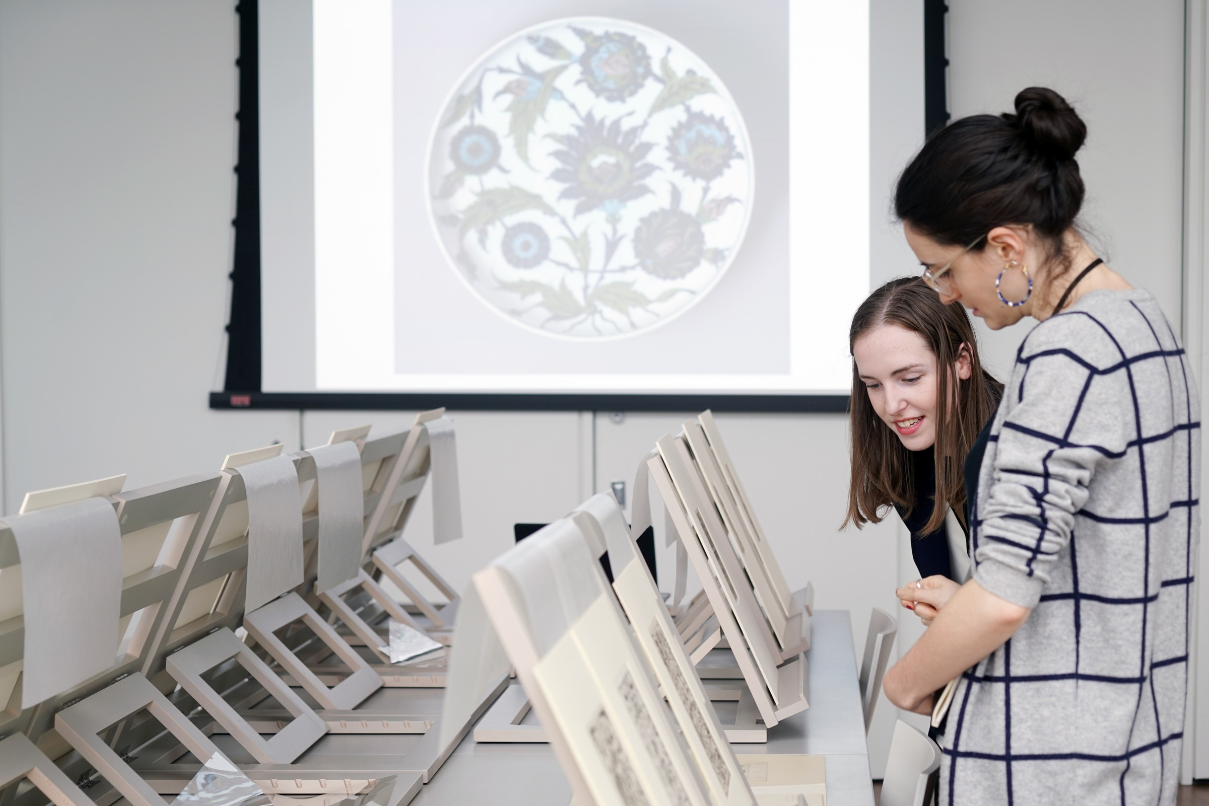 Two women look closely at one of several prints displayed on tabletop easels on a large gray table. In the background on a projector screen is an image of a dish decorated in blue and green flowers.