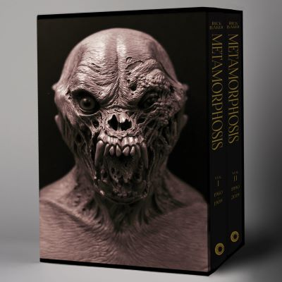 "A slipcase for a two-volume set of books shows the bust of a creepy horror movie creature with wrinkled skin and large teeth. The words ""Rick Baker: Metamorphosis"" runs down the spines of both books."