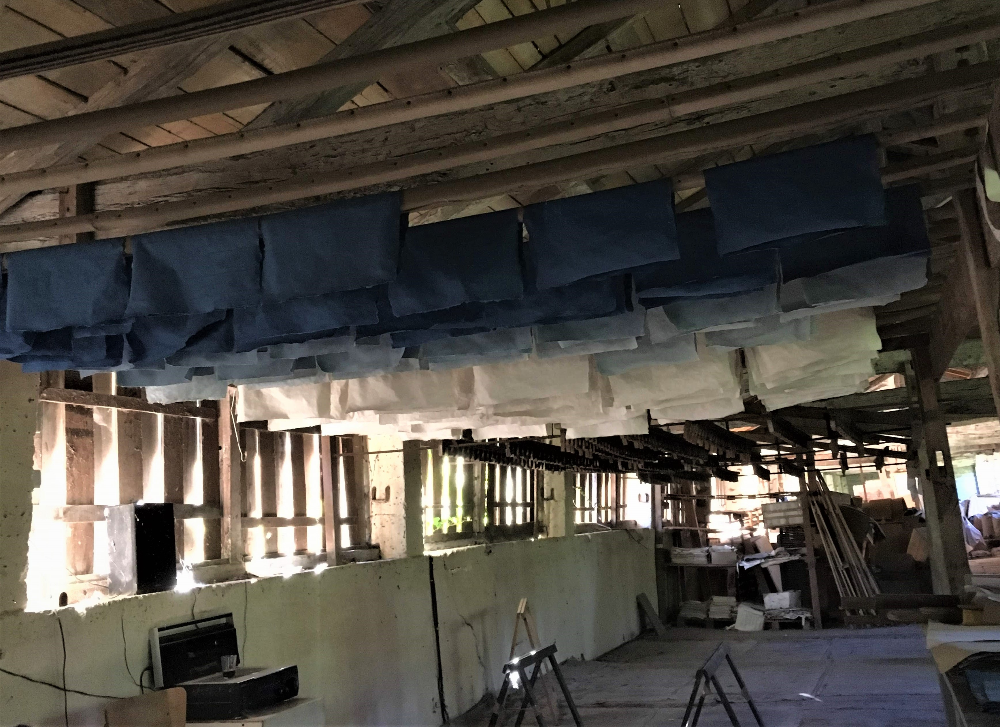 In a large room with a wooden floor, many pieces of blue paper and off-white paper are folded over slim wooden poles that run horizontally under the roof. To the left are vertical wooden slats partially open to let in sunlight.
