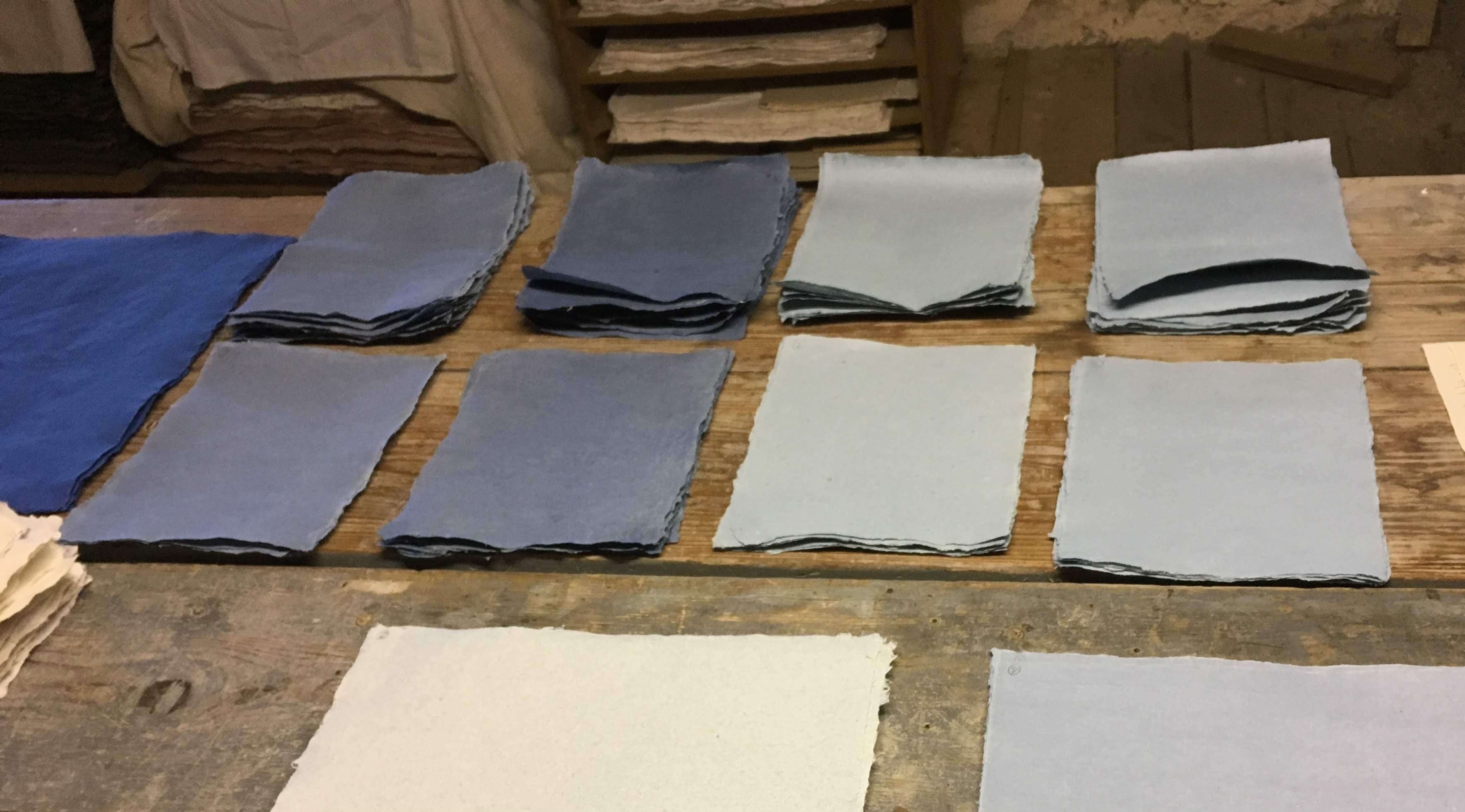 Ten small stacks of different colored blue papers lay on a rough wooden table. There is a very bright blue paper cut off at far left and in the foreground one of the stacks is off-white.