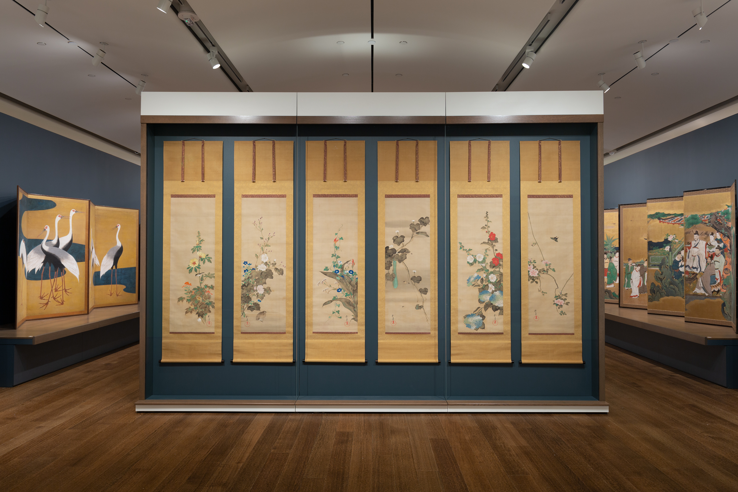 A gallery entrance features a large display case of six hanging scrolls, containing imagery of flowers and branches with leaves, flanked by large folding screens.
