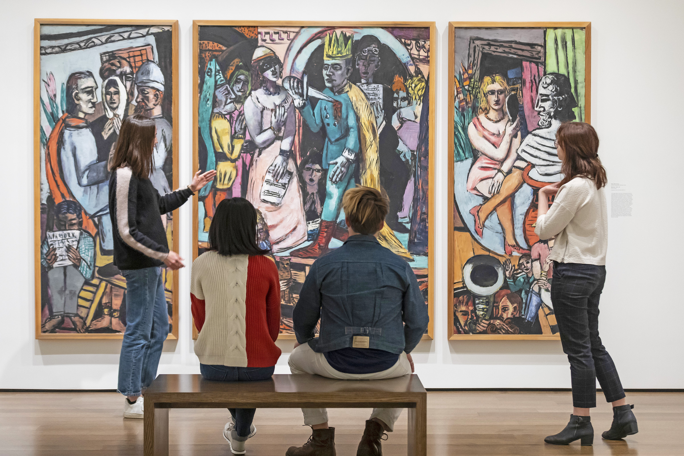 At left, a young woman gestures in front of a large expressionist triptych painting. Two people sit on a bench with their backs to the viewer, and a young person is standing at far right. The painting shows many colorful, shadowy figures in a performance.