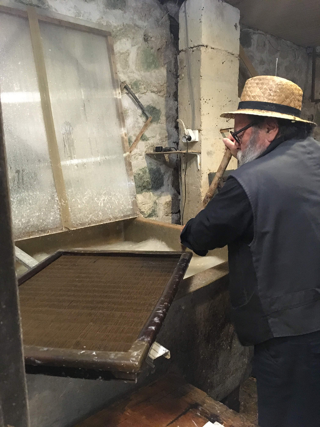 Jacques Bréjoux, wearing a straw hat, black glasses, and black clothing, holds a large stick that is submerged into a vat. He is stirring the foamy-looking contents of the vat; resting flat in the foreground is a dense wire screen in a wooden frame.