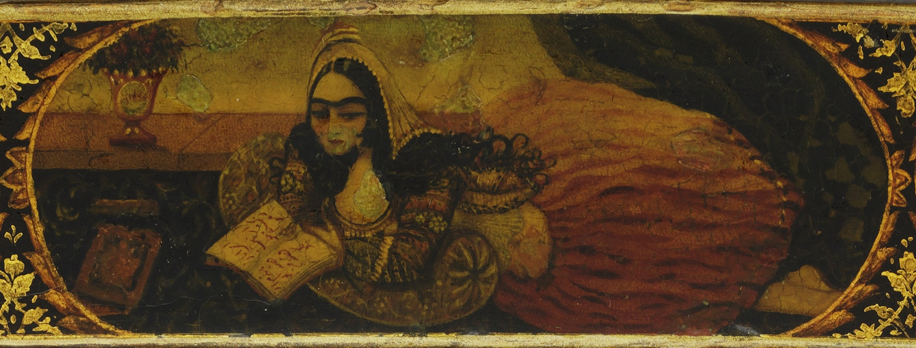 A young woman lies prone on a floral carpet, her elbows are propped up on a cushion, and her hands hold a book with Persian writing. She wears elaborate clothing, including a bright red skirt and a head scarf. A vase with flowers is in the background.