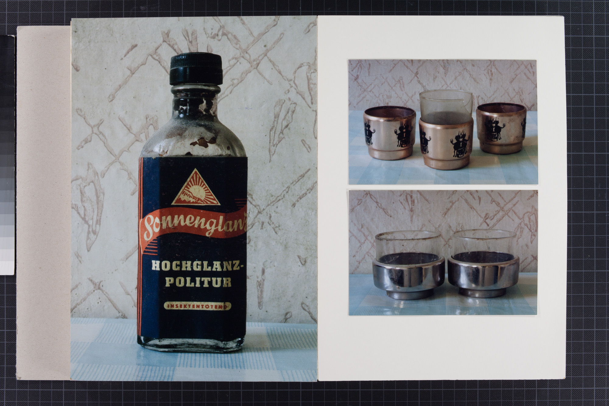 "Three color photographs on an album page show, respectively, a glass bottle of liquid polish labeled ""Sonnenglanz,"" at left; at top right three metal tea glass holders with a black design, the one in the center with a glass in it; and at lower right two silver metal tea glass holders, both of which have glasses in them. All are placed on a light blue-and-white checkered tablecloth with a backdrop of worn-looking beige wallpaper with brown diagonal crisscross hatching."
