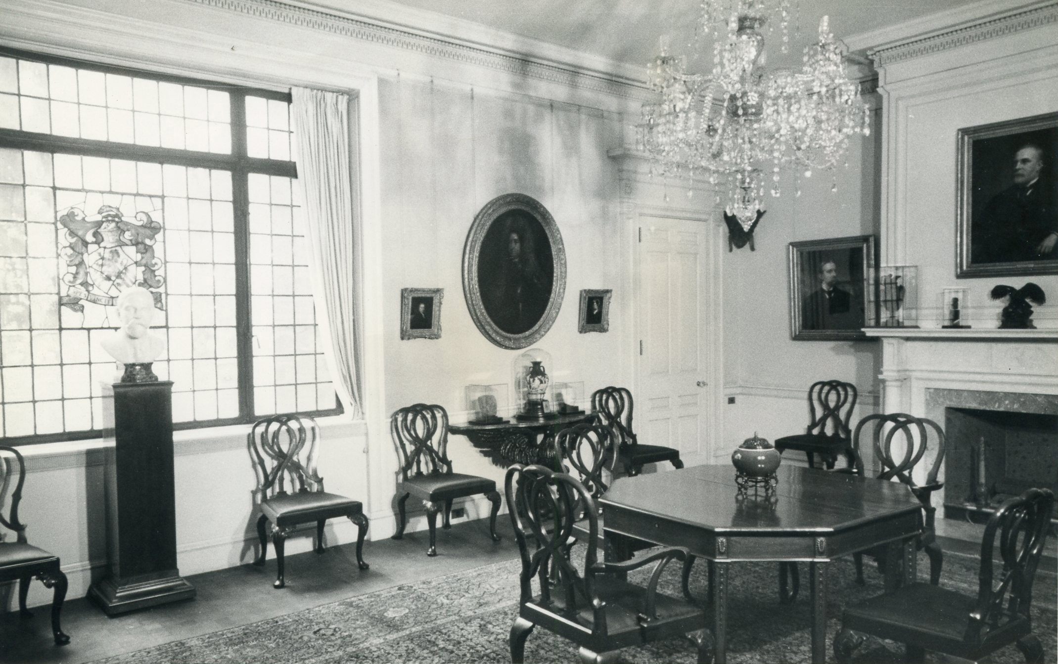 A black and white photograph shows the interior of a dining room. A small table and four chairs are to the right. A window is on the left; at its center is a square of stained glass. Chairs are positioned along the wall; there are several portrait paintings and other decorative objects in the room.