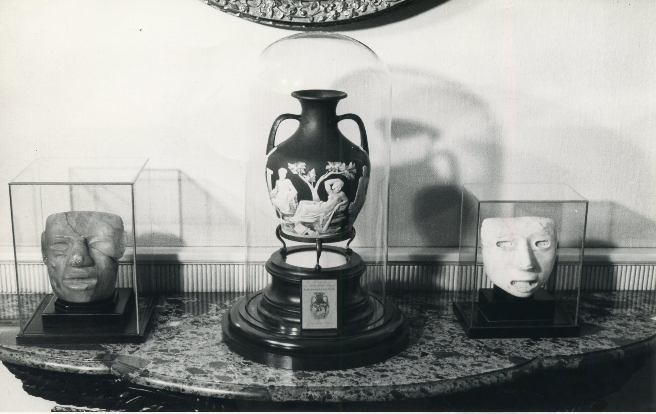 A black and white photograph shows a table attached to a wall. Two stone masks under vitrines flank a low relief vase featuring figures and a tree, also under a vitrine.