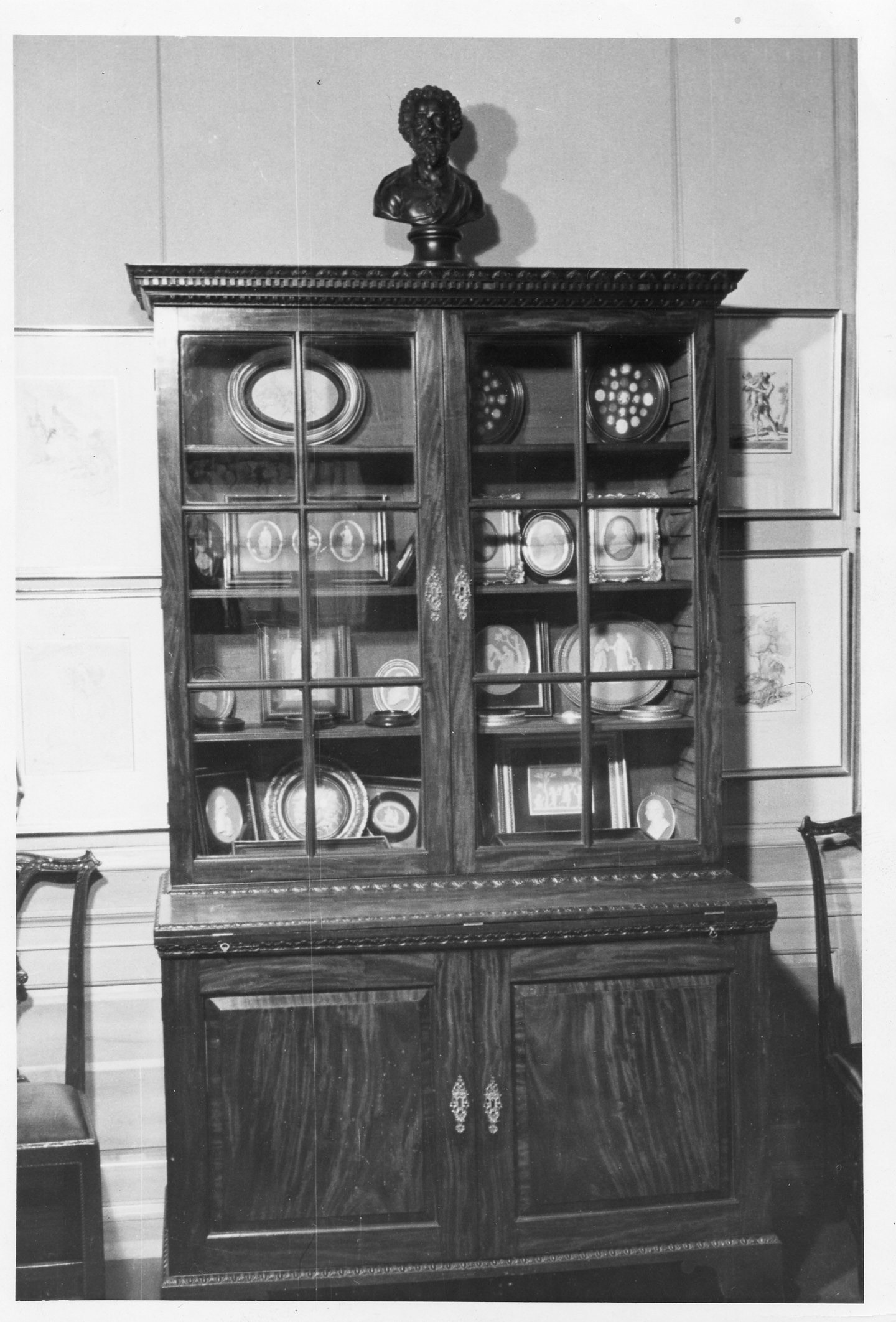 A black and white photograph shows a wooden cabinet with glass doors against the wall. The cabinet is filled with medallions and a bust is on top.
