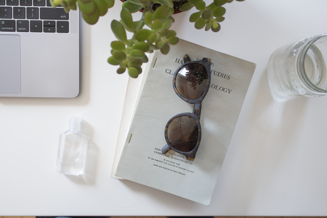 A pair of tortoise-frame sunglasses sits atop a thin stack of books. A small bottle of hand sanitizer and the bottom-left corner of a laptop keyboard appear to the left. Leaves from a potted plant appear slightly out of focus at the top.