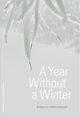 """A book cover shows snow-covered plant matter and crystallized frost along the top, against a white background. The words """"A Year Without a Winter"""" and """"Edited by Dehlia Hannah"""" appear below."""