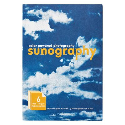 """The cover of a kit folder shows an image of a blue sky with fluffy white clouds. The words """"solar powered photography"""" and """"sunography"""" appear in the center. In the bottom left-hand corner, the words """"6 90lb / 185gsm paper sheets"""" appear within a yellow graphic."""
