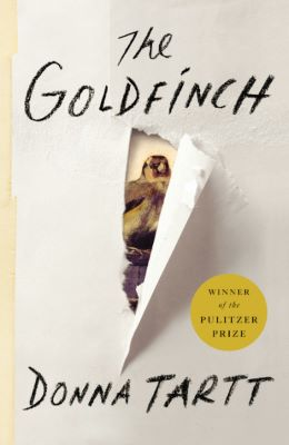 """A book cover shows a mostly white trompe-l'oeil painting of a torn book cover. The painting reveals a goldfinch perched between the roughly ripped sides of a tear running down the middle. The words """"The Goldfinch"""" appear above the bird, and """"Donna Tartt"""" appears below. A round, gold graphic to the right of the bird includes the words """"Winner of the Pulitzer Prize."""""""