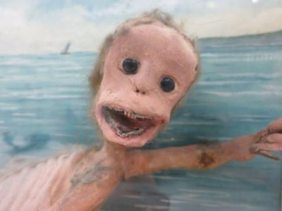 A photograph shows a model of a monkey-like figure, with large black eyes, large forehead, and tiny teeth showing in its wide-open mouth. The creature is set in a small diorama, with a painted blue ocean appearing behind it.