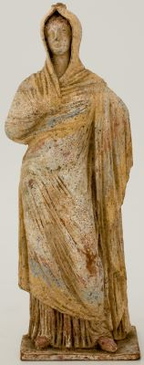 A clay sculpture depicts a standing female figure wearing a long, hooded garment with traces of yellow, orange, and blue pigment. One hand rests at her side, hidden beneath her cloak; the other clutches the neck of her garment.