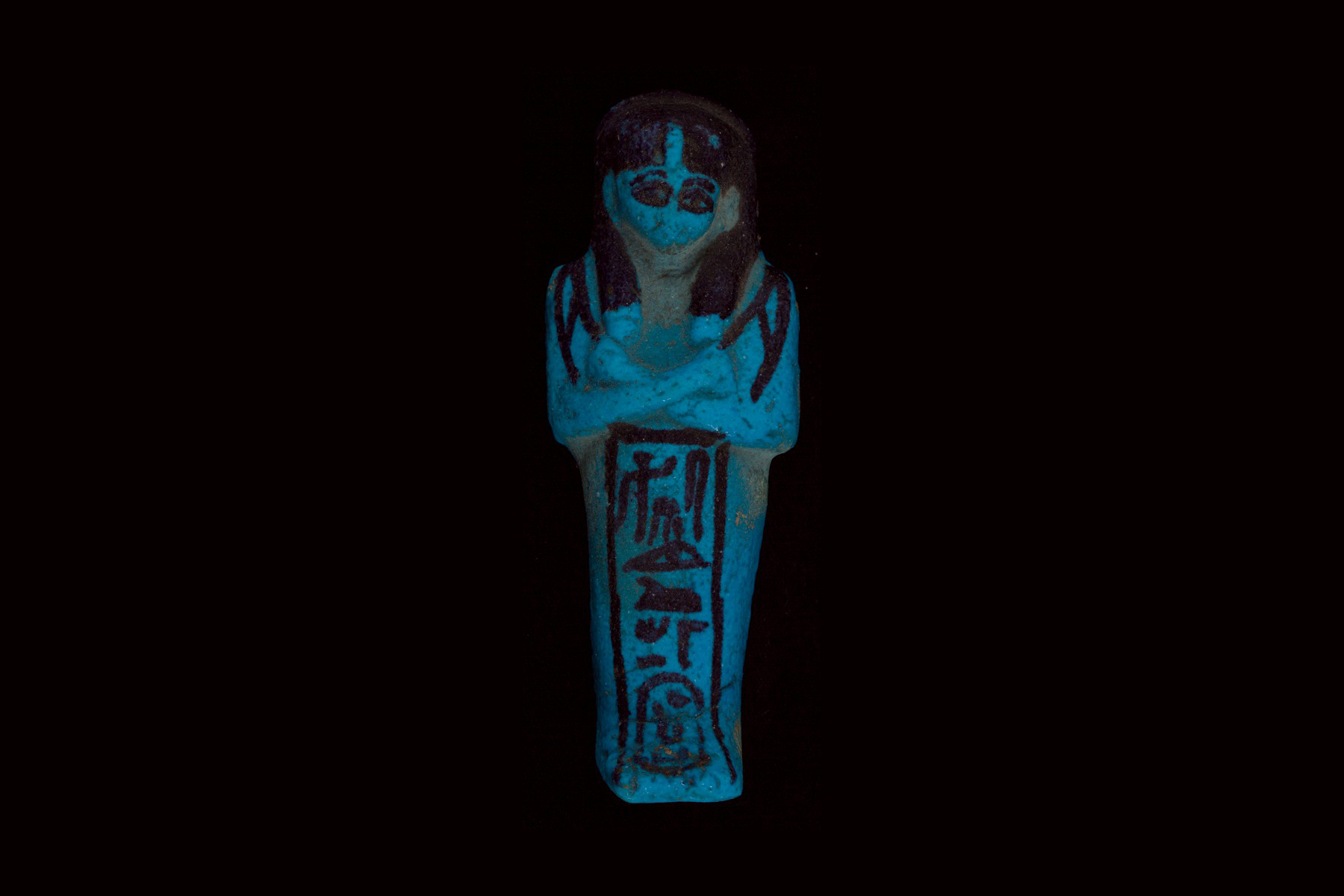 A mummiform figurine of blue faience (ceramic) has painted details in black ink, with a vertical hieroglyphic inscription at the front.