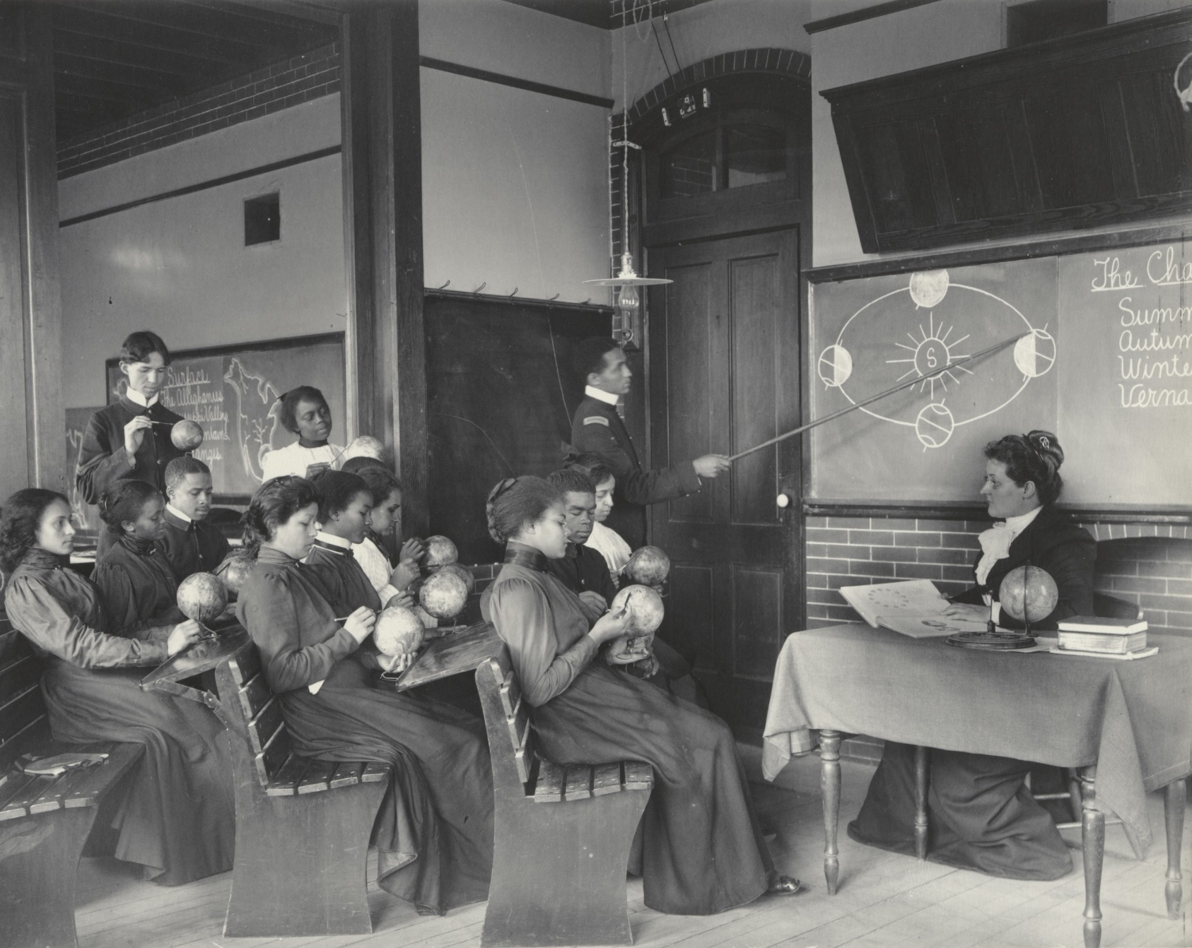 In this black and white photograph, several African American and Native American students sit on benches in a classroom. Each holds a small globe. At right, an African American man stands near a blackboard, holding a long pointer to a chalk drawing illustrating the earth's rotation around the sun. A white woman sits at a desk just underneath the chalkboard. Behind the students is an African American woman standing and looking at the man at the board. A man standing next to her is looking at a globe in his hands.