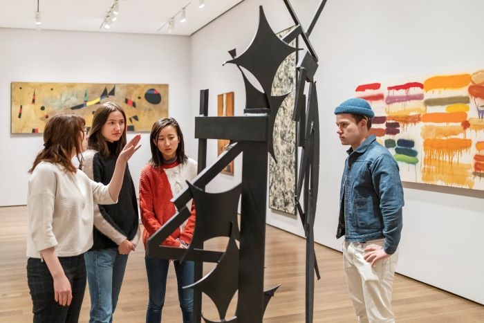 Four college-age students—three women and one man—stand in a gallery looking at a tall wheeled metal sculpture made of bars, curved arcs, and square forms, painted black. Abstract paintings are on the walls nearby.