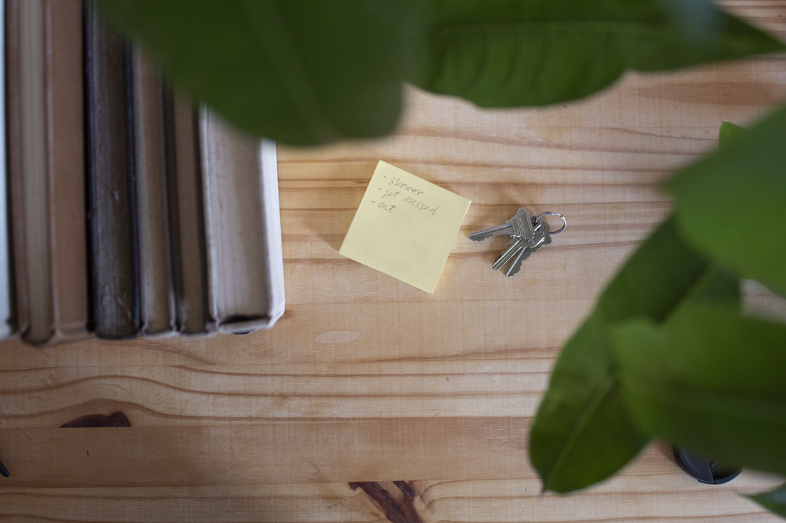 An overview of a wooden tabletop shows the top edges of a group of books, a yellow Post-It note, and a set of keys on a metal ring. Leaves from a potted plant appear slightly out of focus at the top and right. The Post-It note displays the following bullet points in graphite: shower, get dressed, eat.