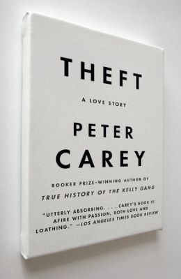 """A book cover shows a white painting canvas mounted on a wall with the following words in bold black lettering: """"Theft"""" and """"Peter Carey,"""" with the words """"A love story"""" in between. The mention of a Booker Award and a quote from a review is at the bottom of the cover."""